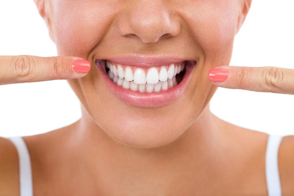 Woman pointing to her beautiful smile at cosmetic dentist in San Jose CA